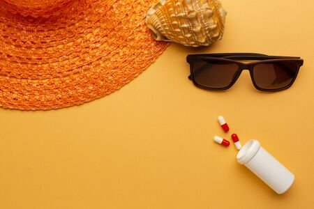 Sunglasses and hat with pills on orange background as a concept of vacation with protection on pandemic situation. Free space for text.
