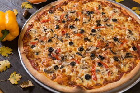 Fresh just made pizza with vegetables, spices for pizza in restaurant. Junk food for lunch with delivery. 免版税图像