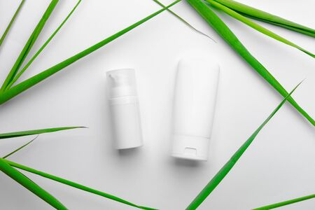 White tubes with face and body cream on white background with green leaves. Special face treatment for summertime with spf. Advertisement concept.