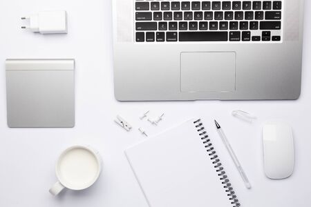 Empty white notebook with pen, working place with keyboard and touchpad. Free white space for notes and text.