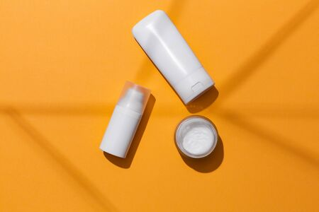 White blank cosmetic products bottles on orange background with free space for text, as advertisement. Concept of sun protection products with spf.