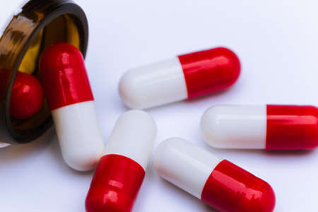 Capsule pills on white background, close-up of a drugs that could give addiction.