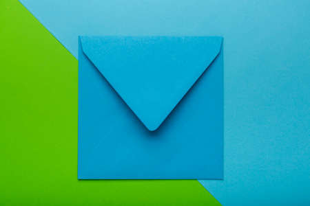 Blue color envelope on green background, as a symbol of getting mail, advertisement element. Corresponds in office, greeting card mockup.