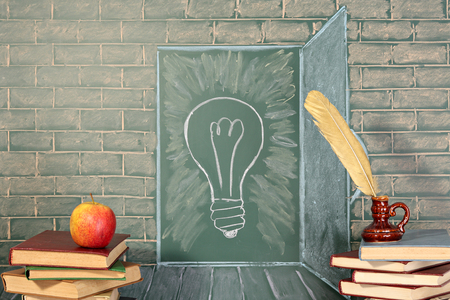 thesaurus: Education unusual concept on chalkboard and books with quill pen and apple Stock Photo