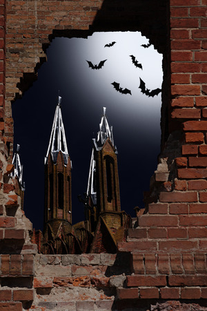 Halloween idea. Night kind through a hole in a wall upon the church and bats in the sky photo