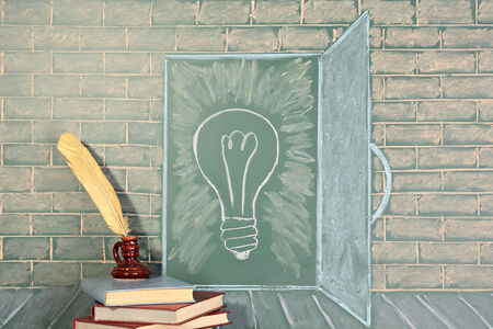 thesaurus: Education unusual concept on chalkboard and books with quill pen Stock Photo
