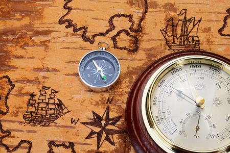 disrepair: Compass and barometer on sea chart on the order of olden time