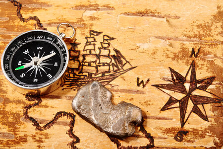 disrepair: Compass and ingot of silver on marine chart on the order of olden time