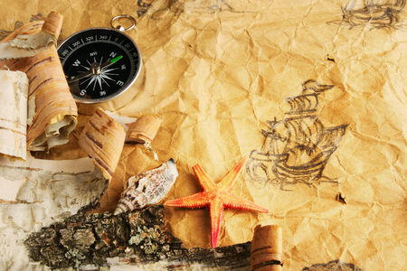 battered land: Still-life. Antique map, shell, starfish and compass Stock Photo