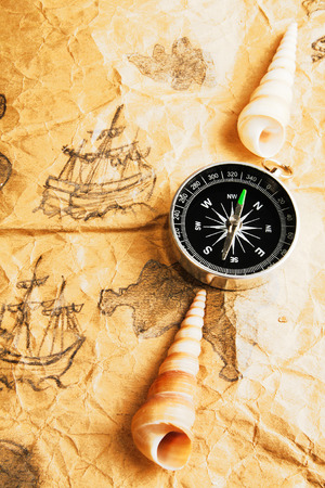 disrepair: Compass and shells on old marine map