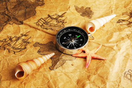 disrepair: Old dingy chart, compass and shells