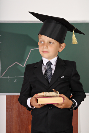 master volume: Schoolboy in mortarboard with book and pencil