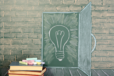 bulb light: Education unusual idea on chalkboard and books with coloured chalks