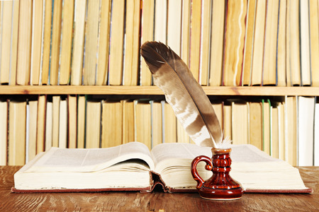 Quill in inkstand on a background of books Stock Photo