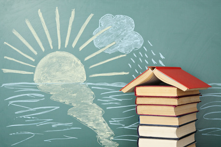 back ground: Unusual education concept. School from books on background of chalk drawing of sun and rain.