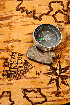 disrepair: Compass and ingot of silver on sea map on the order of olden time