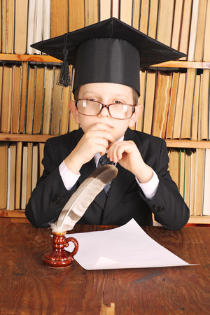 master volume: Unusual joky parody. Child as a professor with quill and paper in library Stock Photo