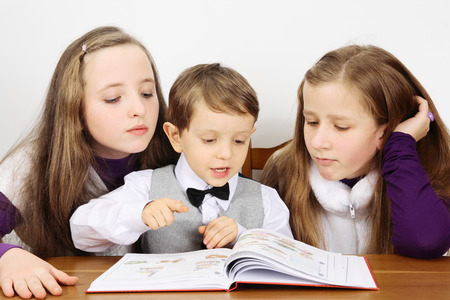 able to learn: Two schoolgirls and little boy in library