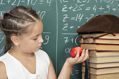 parody: Unusual school concept, schoolgirl with apple and books as a parody on a teacher Stock Photo