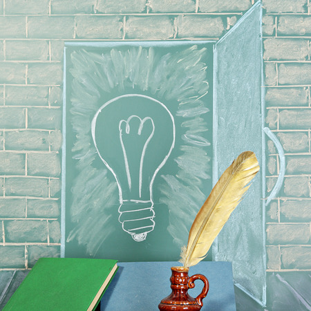thesaurus: Education unusual concept. Blackboard with drawing of bulb and books with quill pen
