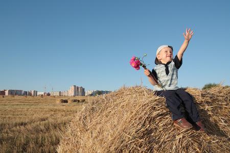 gleeful: Boy gleeful atop of stack Stock Photo