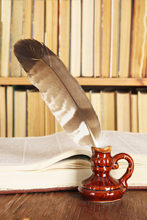 inkstand: Vintage still-life. Quill in inkstand on a background of books