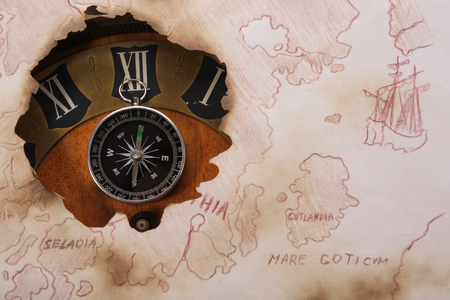 Concept about space and time. Old chart of North Europe. Compass and clock photo