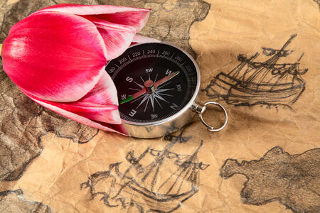 battered land: Compass in tulip on a old marine map with image of sailers Stock Photo