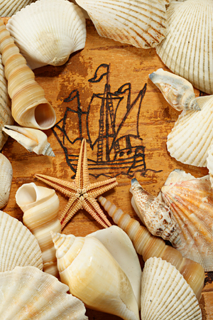 battered land: The ancient sailing ship on a birch bark, shells and starfish Stock Photo