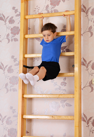 wall bars: The boy of preschool age makes exercise on a gym wall bars