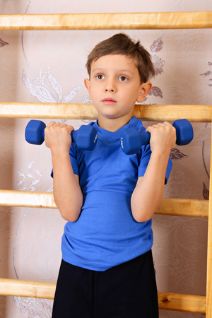 wall bars: The boy of preschool age lifts dumbbells beside a wall bars