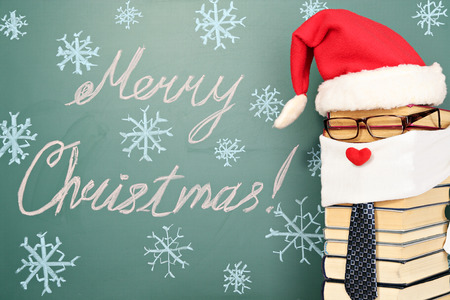 an unusual: Unusual Santa Claus from books before blackboard with title MERRY CHRISTMAS!