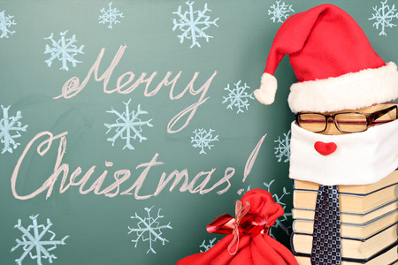 Unusual Santa Claus from books with bag of gifts before blackboard with title MERRY CHRISTMAS! photo
