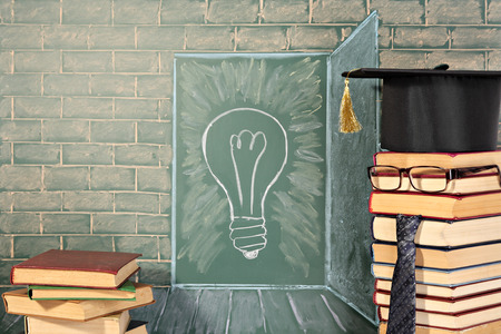 school picture: Knowledge concept with illustration of bulb on chalkboard and teacher from books