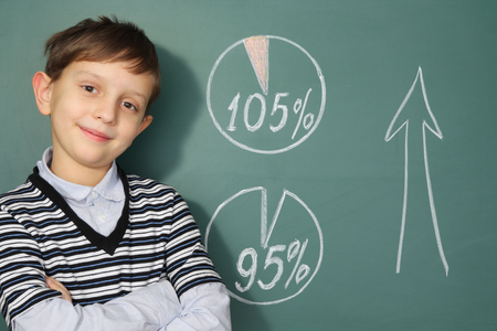 Education concept. Smiling boy before blackboard and diagrams showing success
