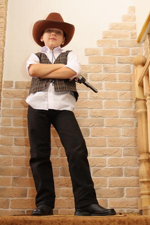 backstairs: Boy as a cowboy posing with gun