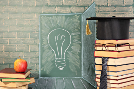 thesaurus: Apple on books and Illustration of bulb on chalkboard behind teacher. Education idea