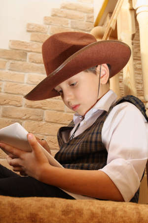 backstairs: Boy as a cowboy reading on a tablet, sitting somewhere in a secluded place Stock Photo