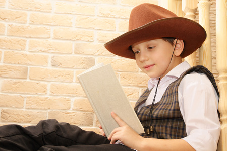 backstairs: Boy as a cowboy reading book Stock Photo