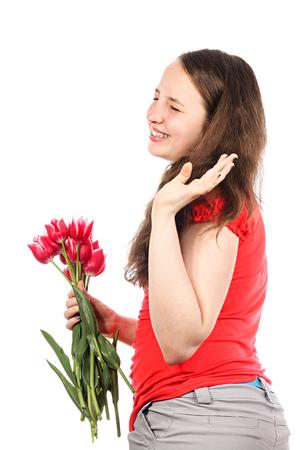 De lachende meisje met bloemen neemt afscheid met gebaar van een hand