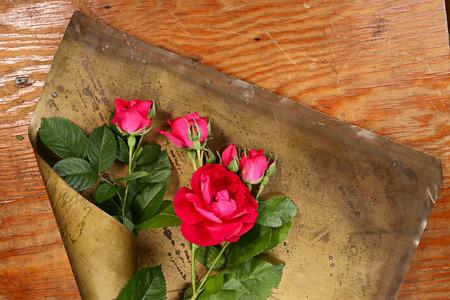 brassy: Art flower composition. Roses on brazen and wood background