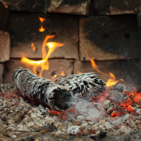 Embers and fire above firebrand in hearth shallow DOF Stock Photo