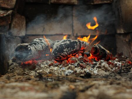 barbaric: Embers and fire above firebrand in hearth shallow DOF Stock Photo