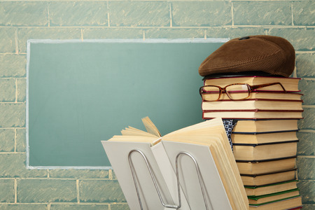 jesting: Unusual jesting teacher reading book before blackboard with copy space Stock Photo