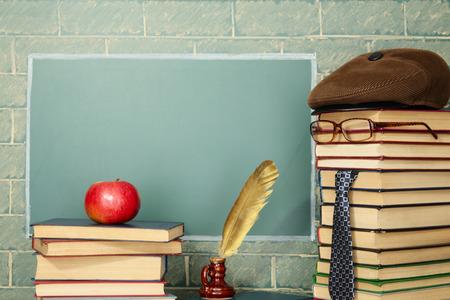Unusual jesting teacher, books, quill pen, apple before blackboard with copy space