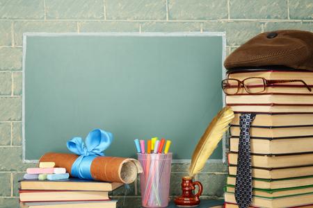 Unusual jesting teacher books quill pen scroll chalk before blackboard with copy space