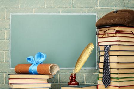 Unusual jesting teacher, books, quill pen, scroll before blackboard with copy space