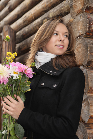 waiting glance: The attractive girl with the flowers, expecting someone behind a corner of a wooden building Stock Photo