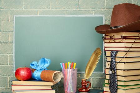 Unusual jesting teacher, books, quill, pen, scroll, apple before blackboard with copy space
