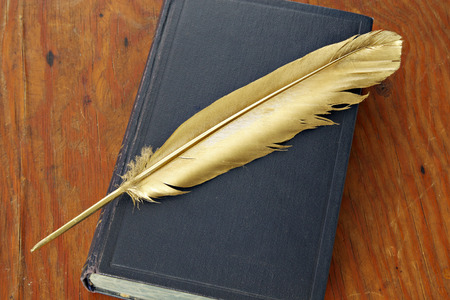 eather: Gold quill pen and antiquarian book on grunge wood board